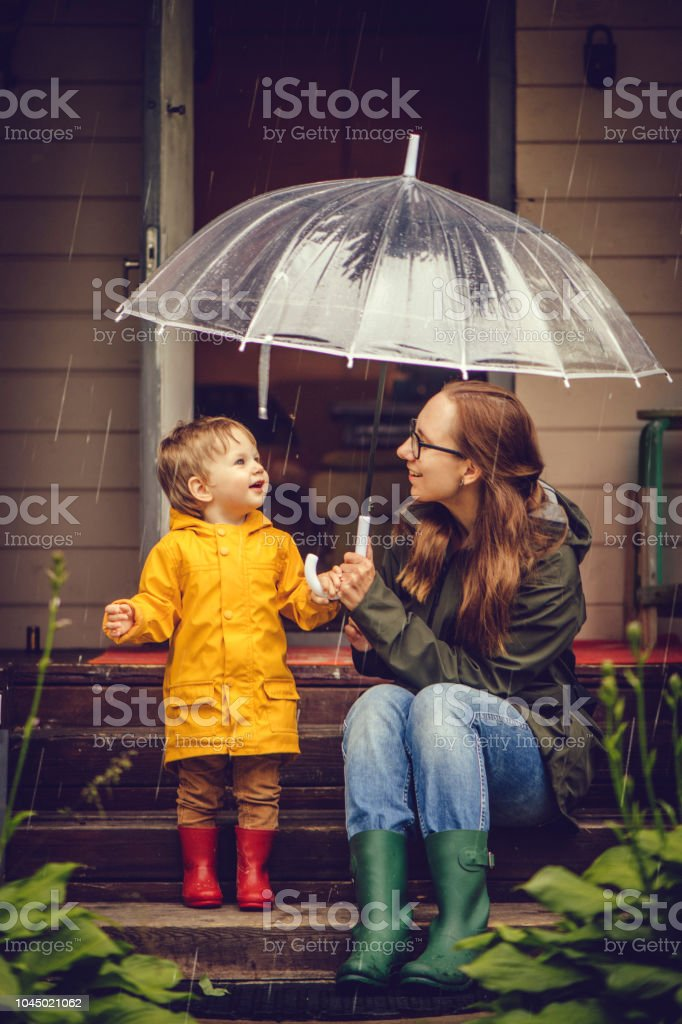 Mother and son in raincoats walking in rain stock photo