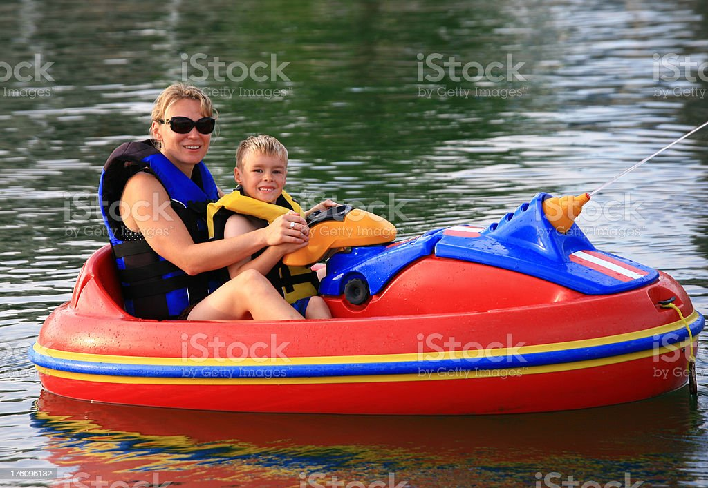 Mother and Son in Recreational Boat with Water Gun stock photo