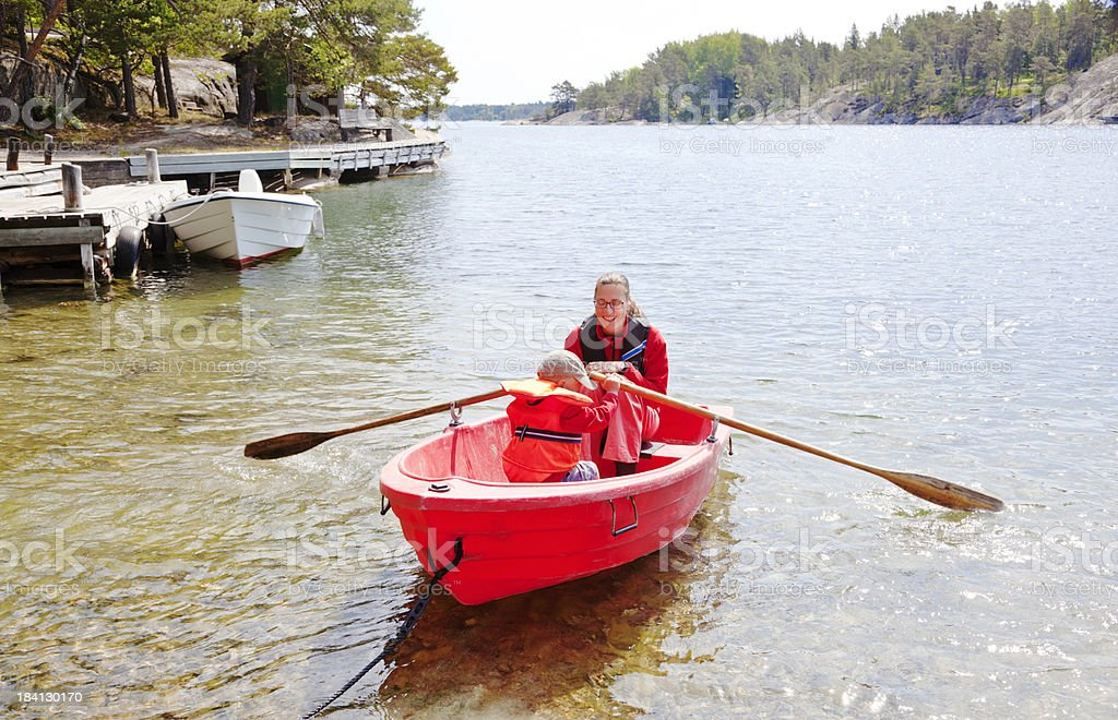 Mother and son in small red rowing boat. Stockholm Archipelago. royalty-free stock photo