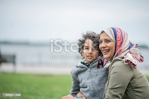Muslim mother and her son embrace and enjoy time in the city together.