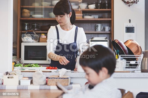 Japanese mother cooking in the kitchen and her son waiting for meal with using a digital tablet.
