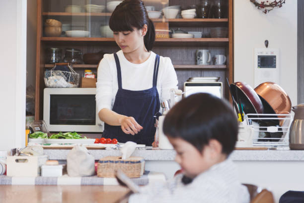 Mother and son in the dining kitchen at home Japanese mother cooking in the kitchen and her son waiting for meal with using a digital tablet. only japanese stock pictures, royalty-free photos & images