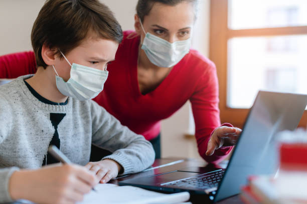 Mother and son in video chat with teacher wearing masks stock photo