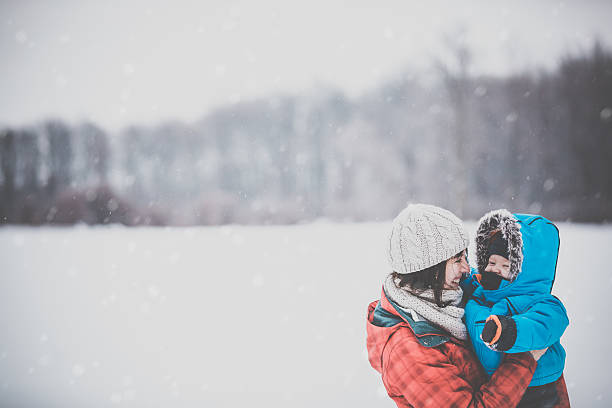 Mother and Son in Winter Forest Snowstorm stock photo