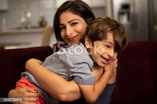 A mother and son inside their home.  They are on a couch.  They are happy and smiling.  The son has shaggy hair and wears a collared shirt and orange / red shorts.  The mom has long dark hair and a wears a dark sleeveless shirt.  They are Iranian ethnicity.  They are embracing and hugging.  The mother looks at camera.