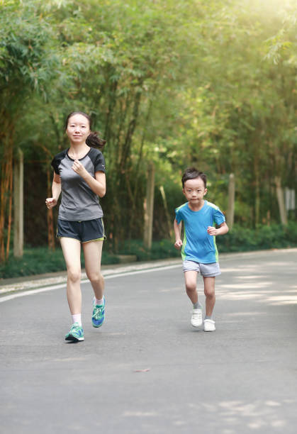 mother and son jogging outdoors stock photo