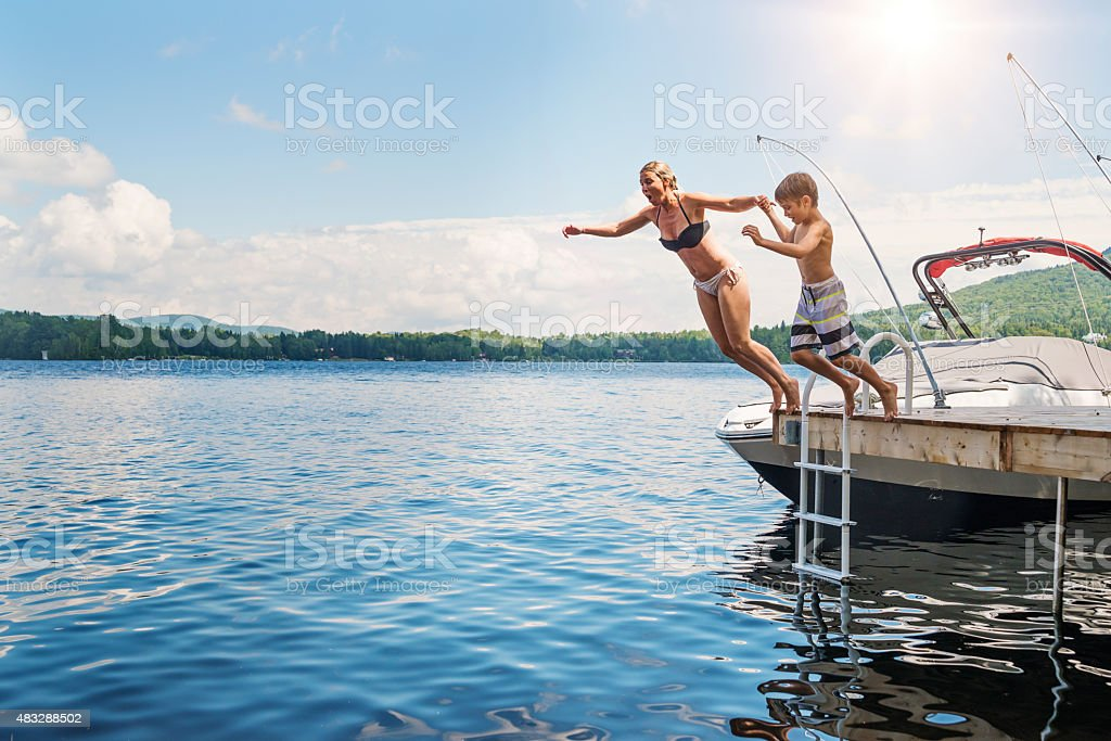 Mother and son jumping in lake from pier sunny day. stock photo