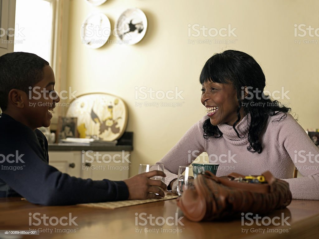 Mother and son (12-13) laughing at kitchen table royalty-free stock photo