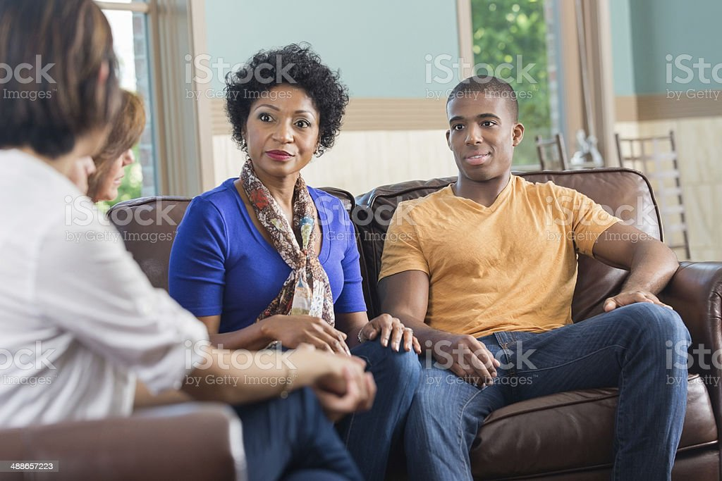 Mother and son listening to advice in support group stock photo
