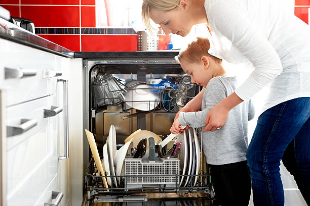 Mother and son loading dishwasher Young mother and her son loading a dishwasher in the kitchen dishwasher stock pictures, royalty-free photos & images