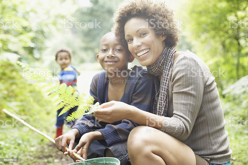 Mother and son looking at fern leaf stock photo