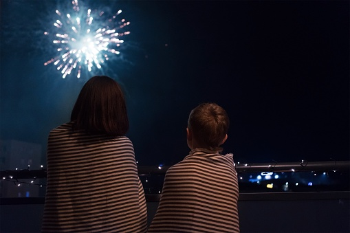 Mother and son looking at New Year celebration fireworks in nigh