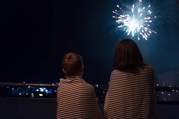 Mutter und Sohn mit Blick auf Silvesterfeier Feuerwerk in Nachthimmel warm eingehüllt in gestreifte Plaids stehen auf dem heimischen Balkon. – Foto