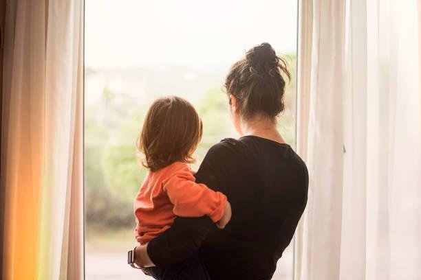 mor och son tittar ut ur fönster - förälder bildbanksfoton och bilder