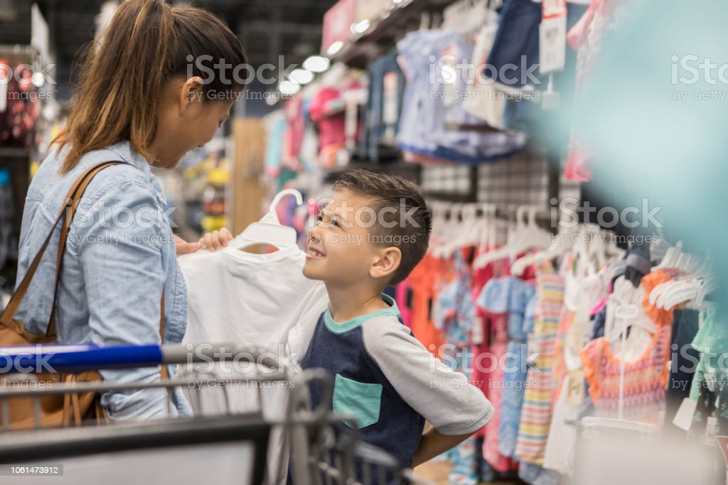 Mother and son make eye contact while looking for new clothes stock photo