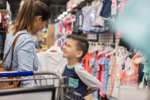 Mutter und Sohn Blickkontakt während der Suche nach neuen Klamotten – Foto