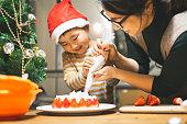 一緒にクリスマスケーキを作る母と息子