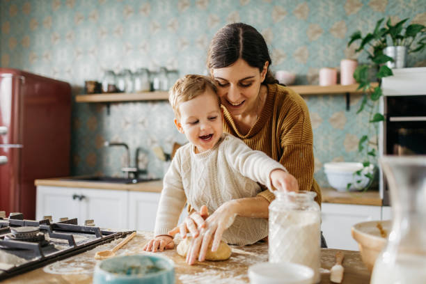 Mother and son making dough together stock photo