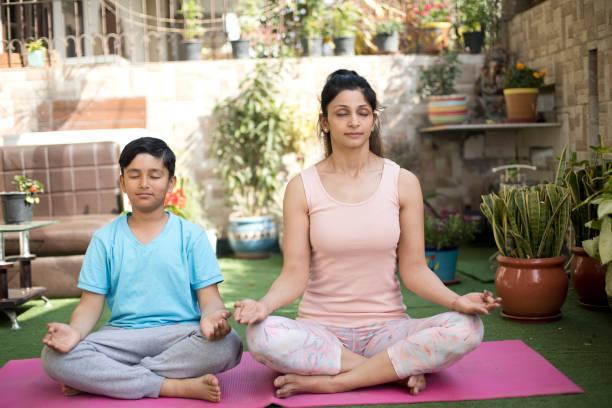 Mutter und Sohn meditieren auf Übungsmatte – Foto