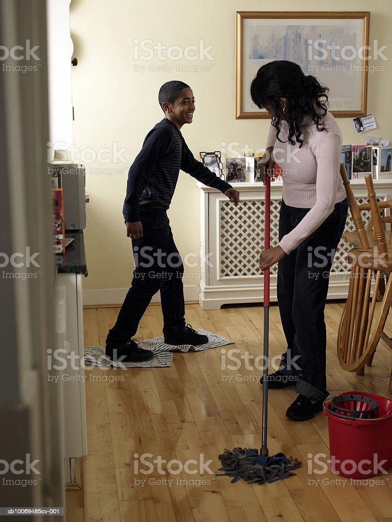 Mother and son (12-13) mopping and drying kitchen floor royalty-free stock photo