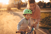 Photo of a young boy and his mother on a bicycle lane, learning to ride a bike.