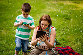 Mother And Son Searching The Web , Each Of Them On Own Devices, Son Using Phone And Beautiful Woman Using Digital Tablet, While Resting On Picnic Blanket In Forest On Leisure Summer Day.