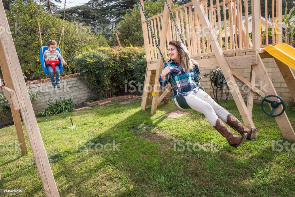 Mother and son on swing set stock photo