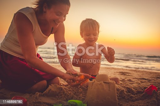 Little boy and mother building a sandcastle on the beach  in summer