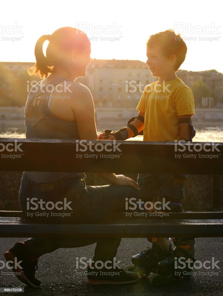 Mother and son on the bench by the river. stock photo