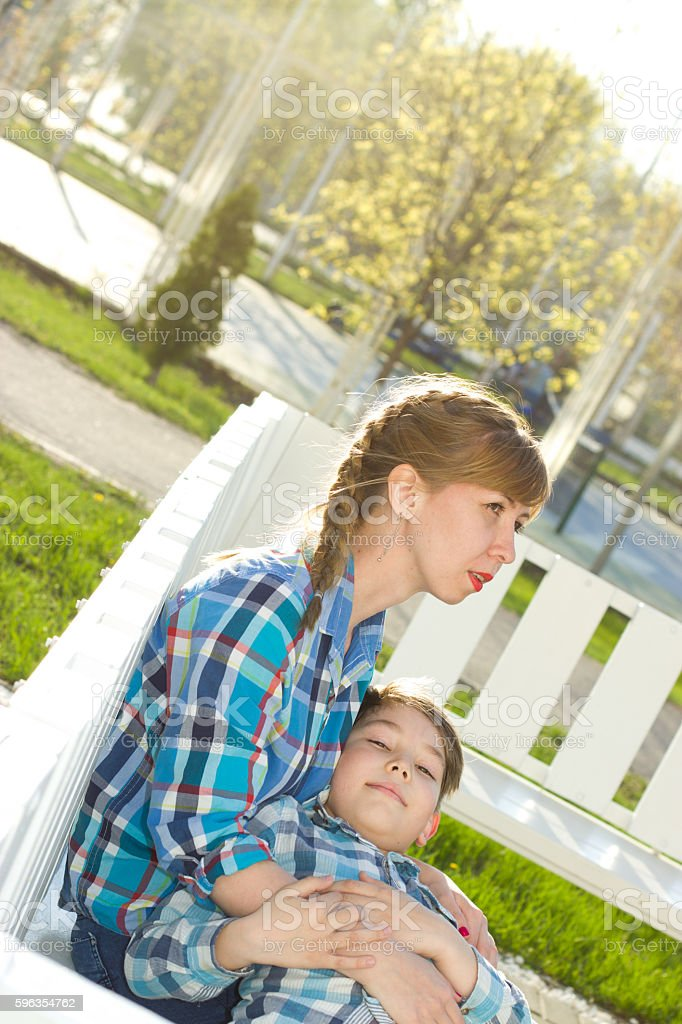 Mother and son on the bench in the park royalty-free stock photo