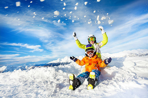 Mother and son on the mountain happy throw snow Mom and child with ski outfit mask and helmet sit and throw up snow ski holiday stock pictures, royalty-free photos & images