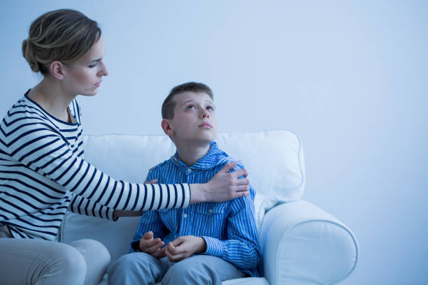 mother and son on the sofa - autism stock photos and pictures