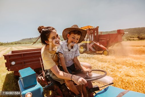Mother and son on the tractor during harvesting