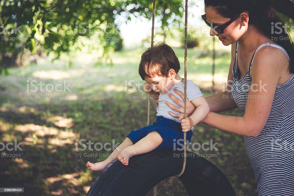 Mother and son on tire swing stock photo