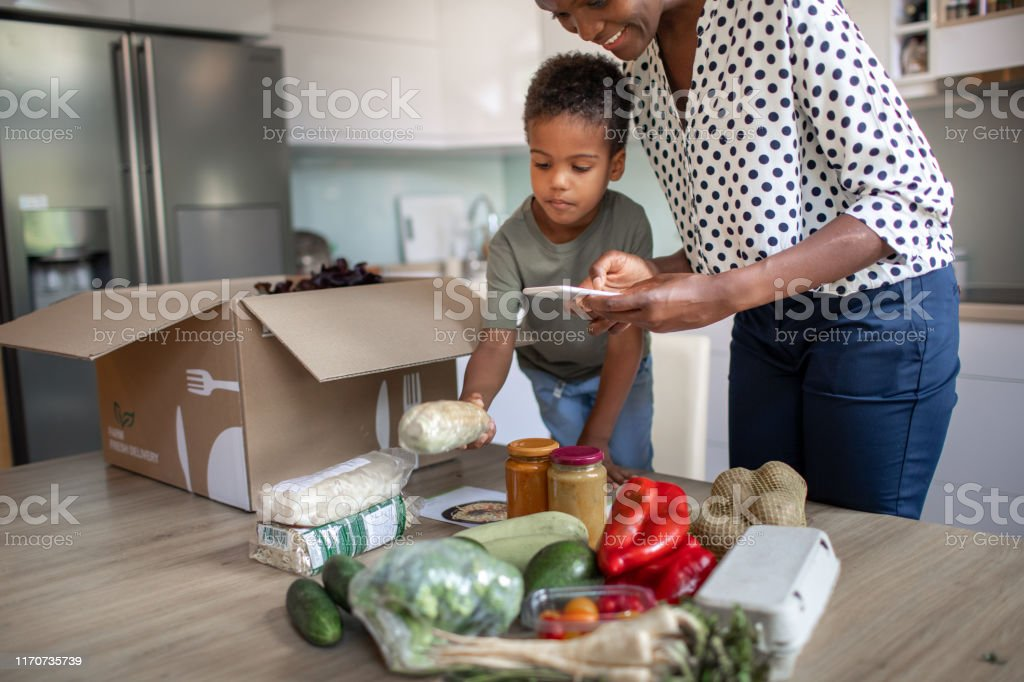 Mother And Son Opening Parcel With Meal Kit - Royalty-free 4-5 Anos Foto de stock