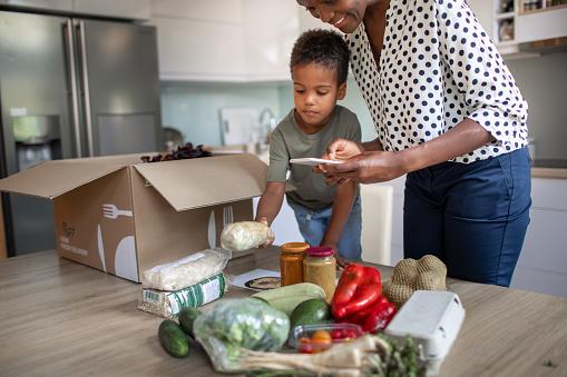 Mother And Son Opening Parcel With Meal Kit - Fotografias de stock e mais imagens de 4-5 Anos