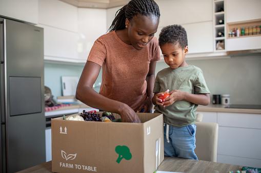 母と息子はミールキットで小包を開きます - 2人のストックフォトや画像を多数ご用意