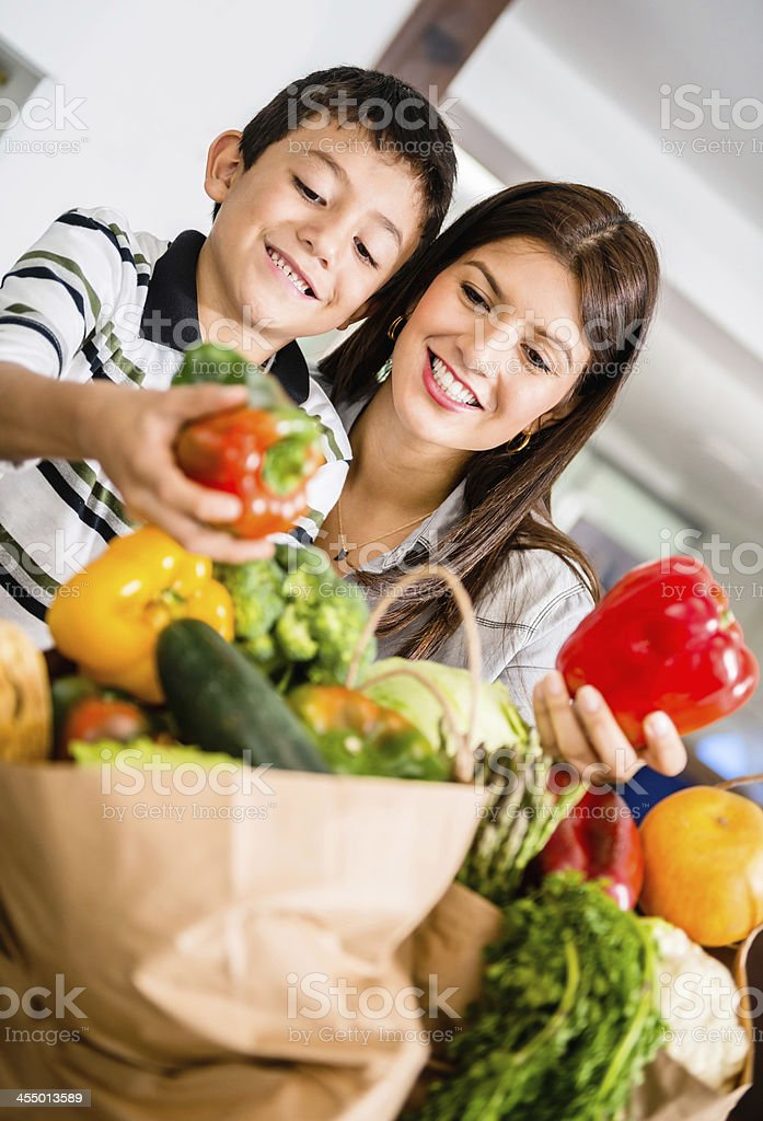 Mother and son organizing groceries stock photo