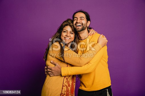 Portrait of a mature Asian woman and her son embracing in front of a purple background.