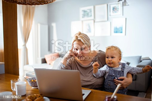 Close up of a mother having breakfast with her son and working on her laptop from home