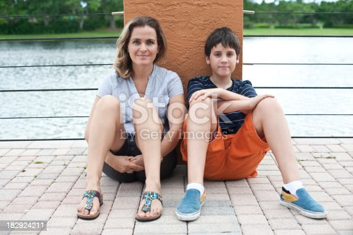 Caucasian mother and her son posing by the river banks