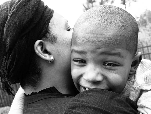 Mother and son Afro caribbean woman carrying her son image in black and white haitian ethnicity stock pictures, royalty-free photos & images