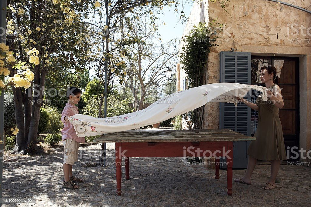 Mother and son (8-9) placing tablecloth on table in pergola royalty-free stock photo