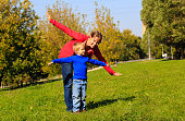 mother and son play in autumn nature