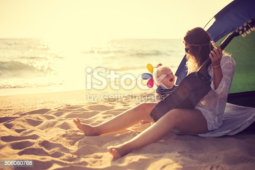 istock Mother and son playing a guitar on the beach 506060768