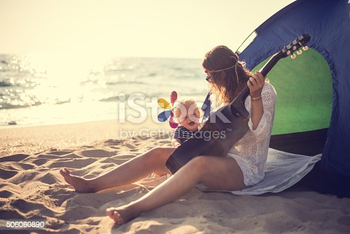 istock Mother and son playing a guitar on the beach 506060890