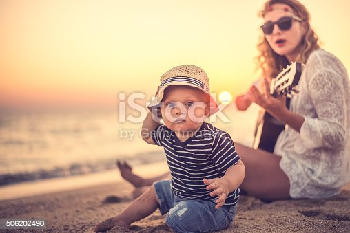 istock Mother and son playing a guitar on the beach 506202490