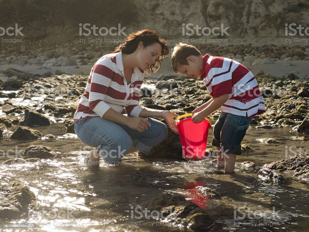 Madre e hijo (6-7) playing at seashore foto de stock libre de derechos