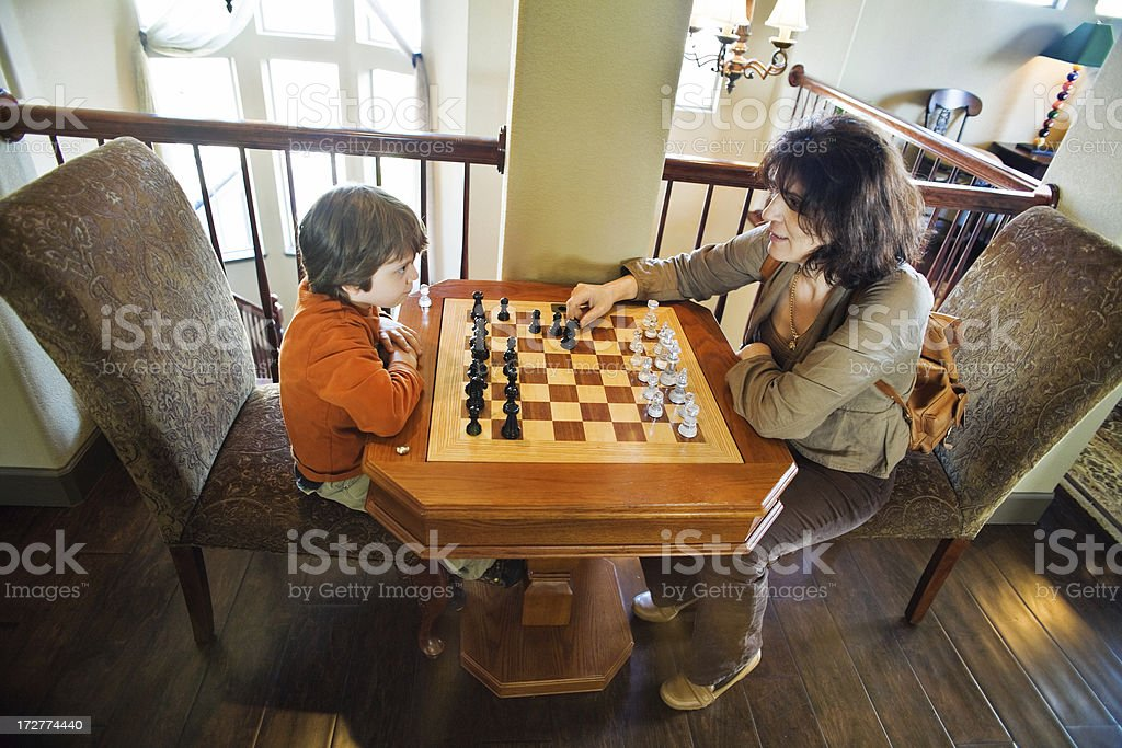 mother and son playing chess together on a brown chessboard royalty-free stock photo