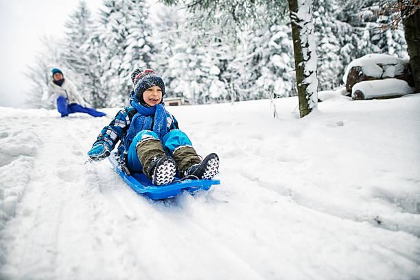 mother and son playing in snow - schneespiele stock-fotos und bilder